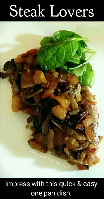 A steak topped with sautéed onion, mushrooms, tomatoes and garnished with baby spinach leaves.